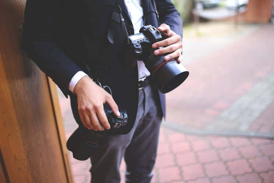 Wedding videographer carrying two cameras