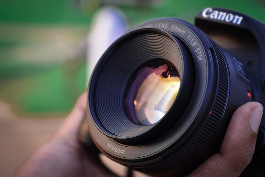 A person touching a Canon 50mm lens