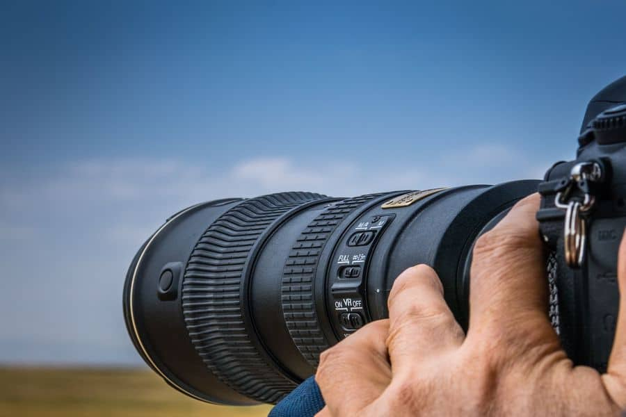 Person using his zoom lens to shoot landscape photos