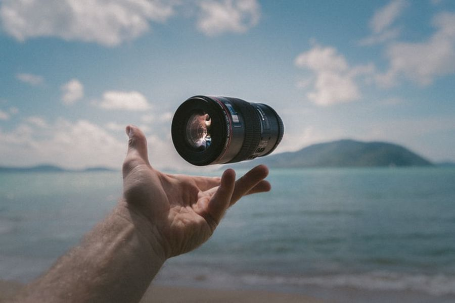 Hand holding a Canon lens that is perfect for shooting landscape images