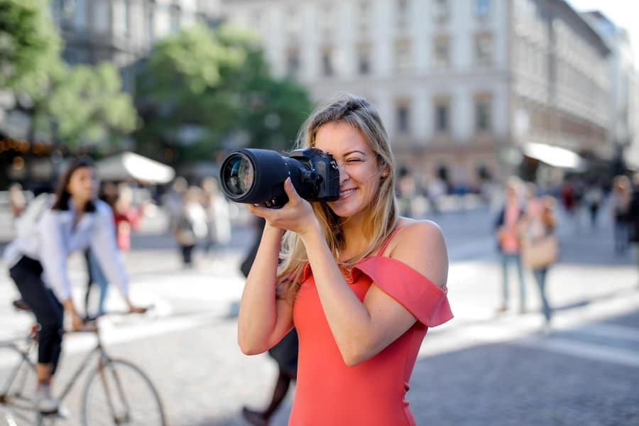 Woman taking photos of a busy street using a Canon camera