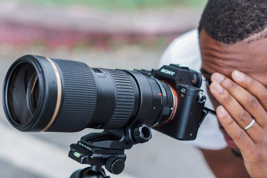 Man looking at his Sony A7RII with long lens