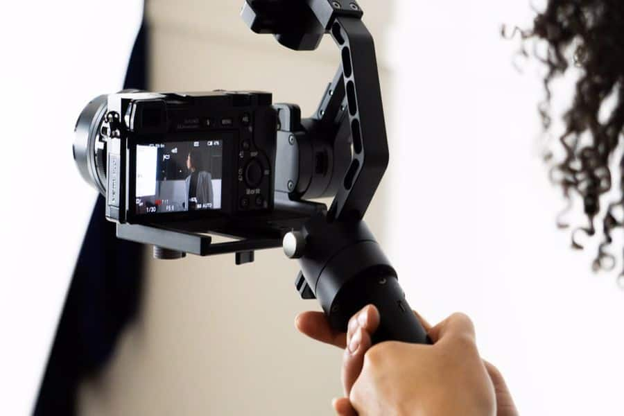 Hand holding a camera attached to a gimbal