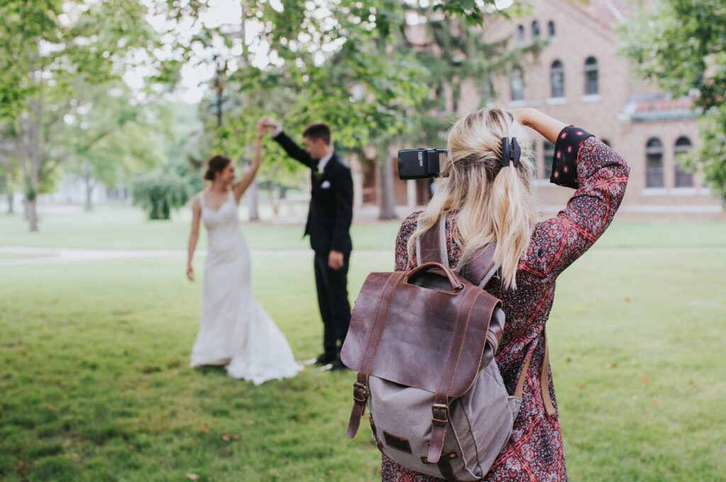 A photographer shooting a couple in wedding dresses outdoors