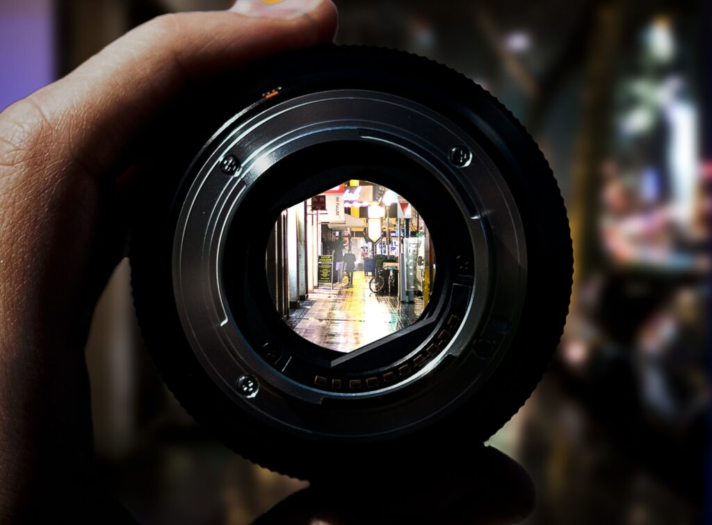 A camera lens being held with an open camera shutter