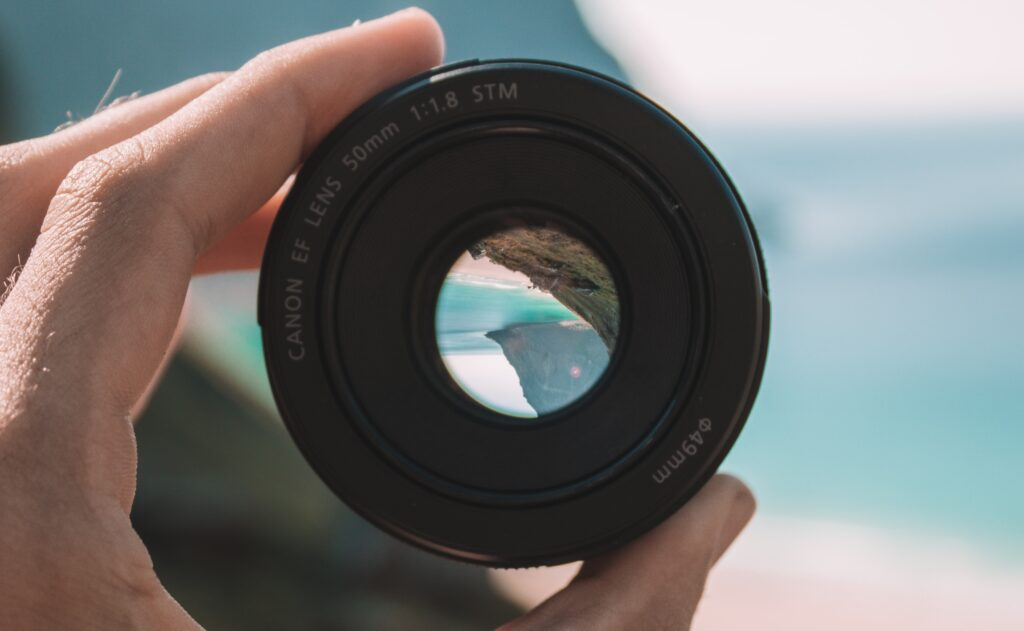 A 50mm lens being held with a landscape background