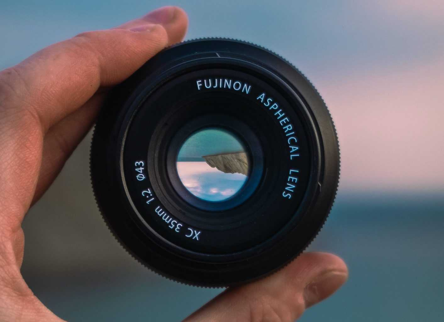 A 35mm lens being held with a blur landscape background