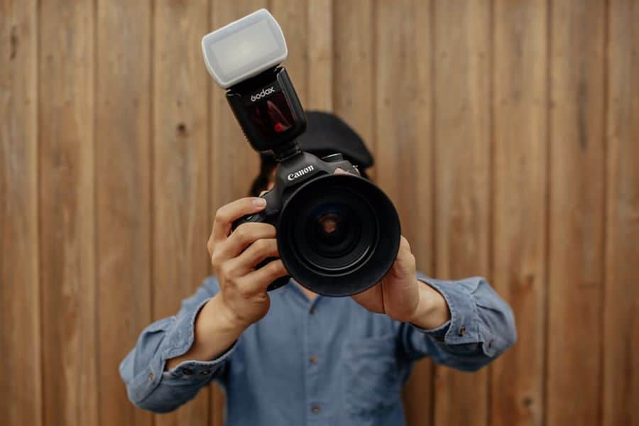 Man holding a Canon camera with an external flash