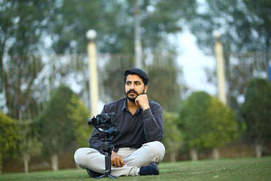 Man sitting on the grass with a camera attached to a gimbal in front of him