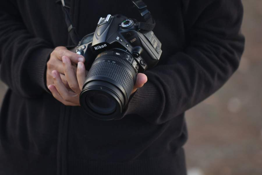A photographer carrying a Nikon camera with sports photography lens