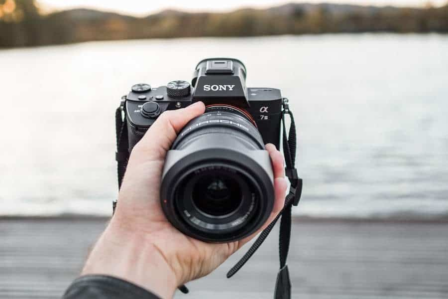 A photographer holding a camera with Sony lens