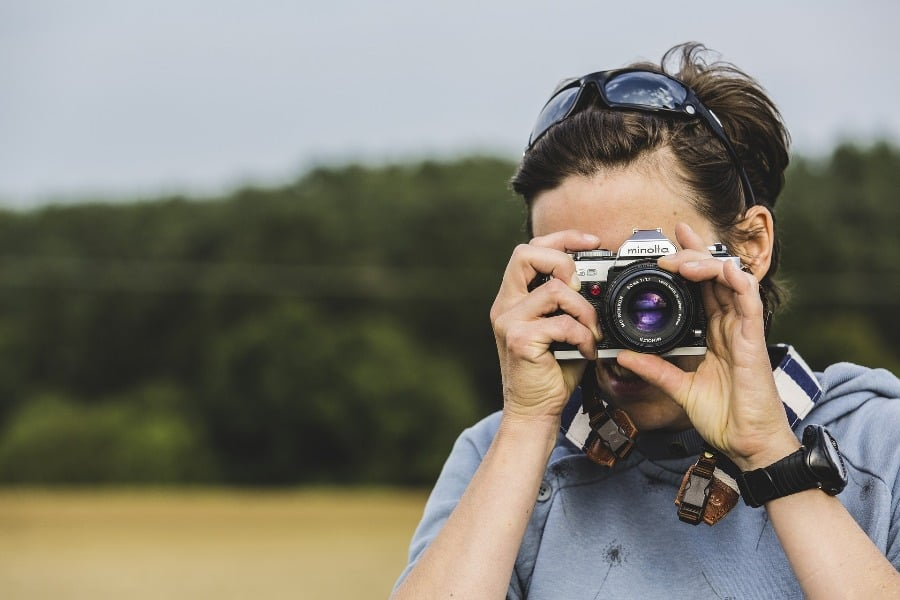 Woman adjusting her camera lens while trying to take a photo