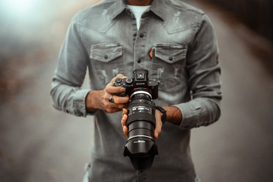 Man holding a DSLR with a telephoto lens