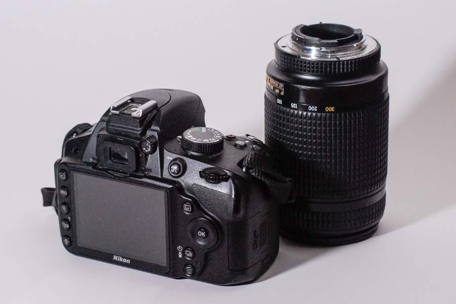 A lens placed beside a D3200 camera