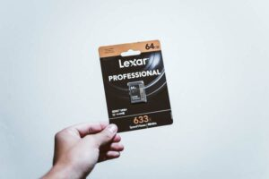 Hand holding a Lexar memory card for Sony A6500 camera