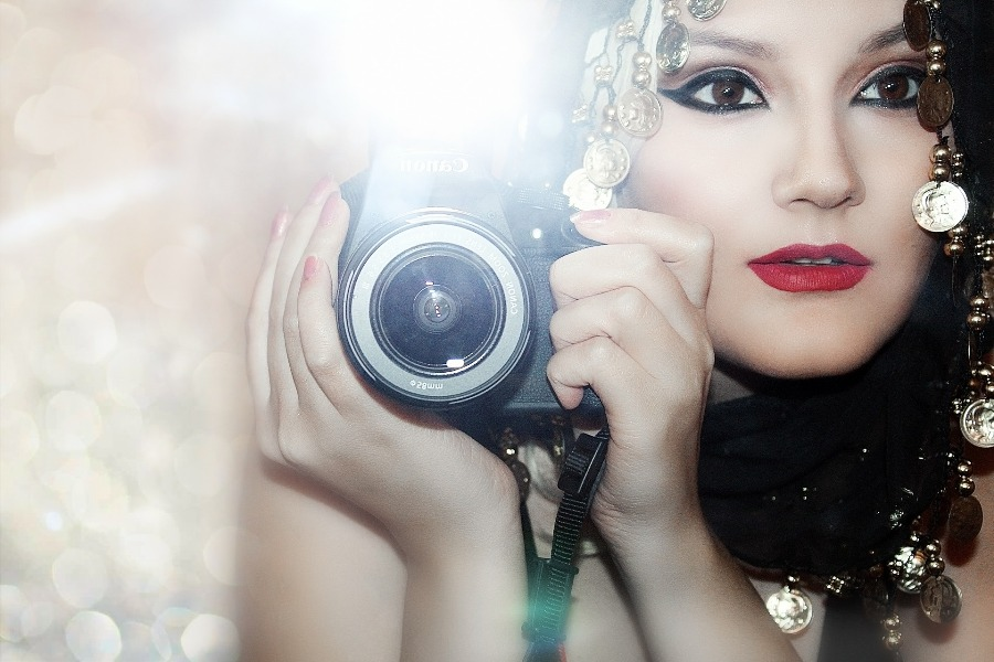 Woman holding a Canon camera with its flash going off