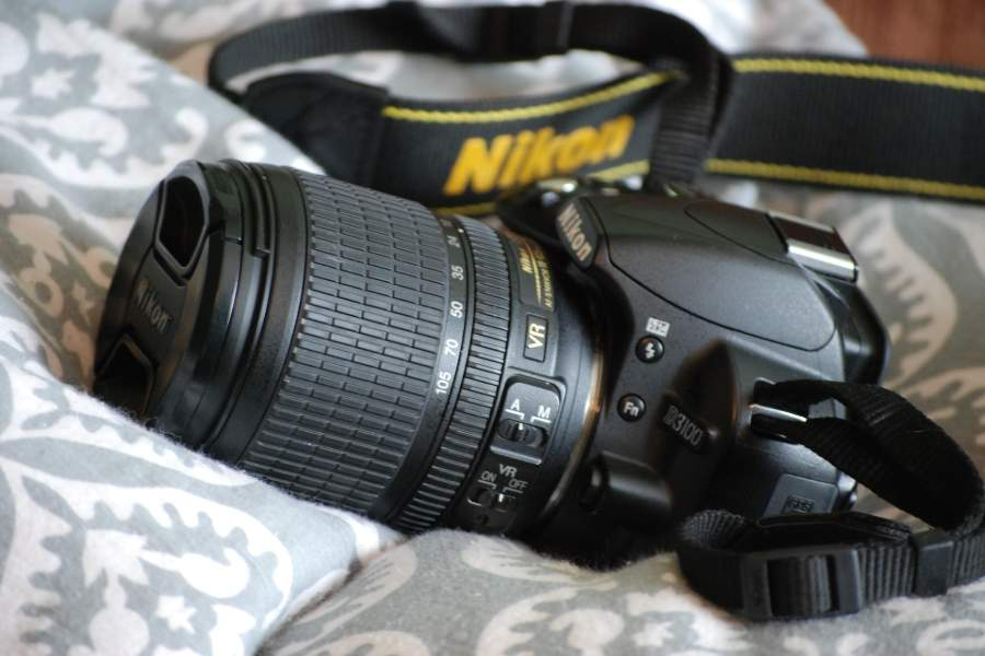 A Nikon D3100 DSLR with lens on a white and gray blanket