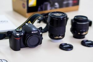 Nikon D60 with two different kinds of lenses beside it