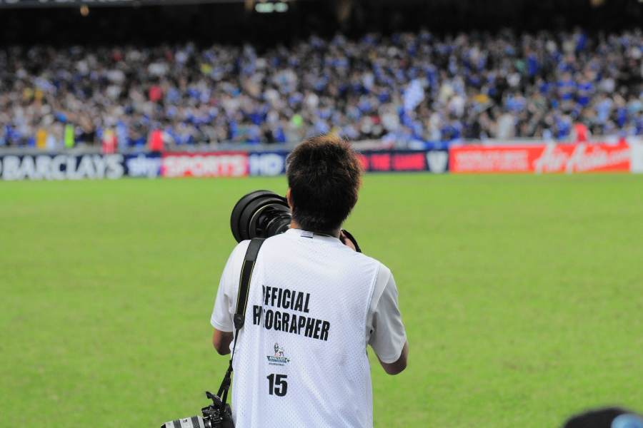 A sports photographer taking pictures at a soccer event